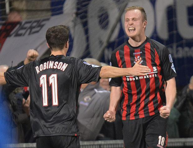 Gr-eight night: Crusaders striker Jordan Owens takes the salute from team-mate Josh Robinson after equalling Glenn Hunter's club scoring record with the third goal in their 3-1 win over Coleraine to go eight points clear at the top of the Danske Bank Premiership