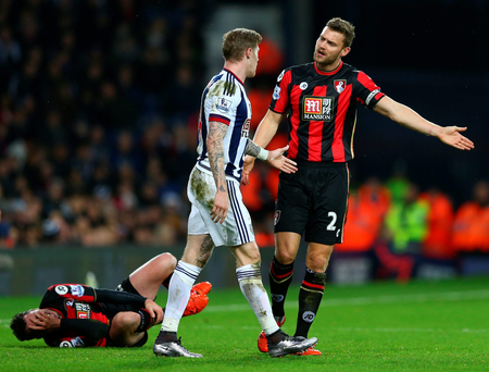 Adam Smith lies on the ground while his Bournemouth teammate Simon Francis argues with James McClean