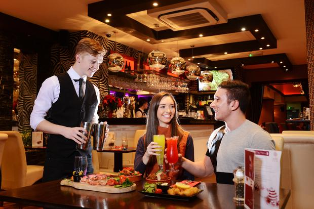 A landmark location in Belfast - known by many as the former Wimpy or Carlton Bar has become the citys newest tapas bar. Solo Kitchen and Bar in Wellington Place will cater for those seeking Spanish tapas, cocktails or a wide range of casual dining. Pictured are Anthony ONeill (waiter) with Zoe Benson from Lisburn and Daniel McCavery from Moira.