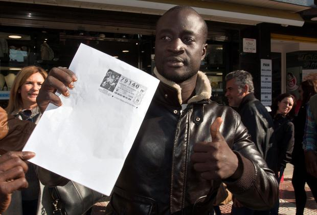 Senegalese Ngame thumbs up as he holds a photocopy of a winning lottery ticket. AFP/Getty Images