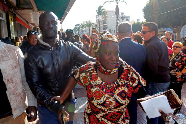 Senegalese Ngame (L) walks with a woman after knowing he is the owner of a winning lottery ticket of the Spanish Christmas' lottery draw. AFP/Getty Images
