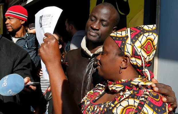 Senegalese Ngame (C) looks at a photocopy of a winning lottery ticket. AFP/Getty Images