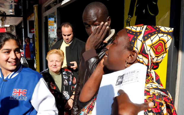 Senegalese Ngame (2nd R) wipes his eyes next to a woma who holds a photocopy of a winning lottery ticket. AFP/Getty Images