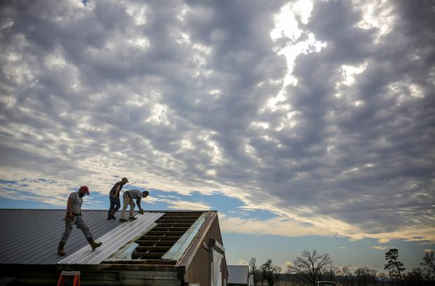 Construction workers John Croft, from left, Michael Edwards and Lee Croft, repair damage to the roof of a chicken house along Arkansas 247 north of Atkins, Ark., near where a woman was killed and a toddler was injured as storms moved through the area Friday morning. (Stephen B. Thornton/Arkansas Democrat-Gazette via AP)