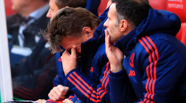 Manchester United manager Louis van Gaal sits dejected on the bench during the Barclays Premier League match at the Britannia Stadium, Stoke. PA