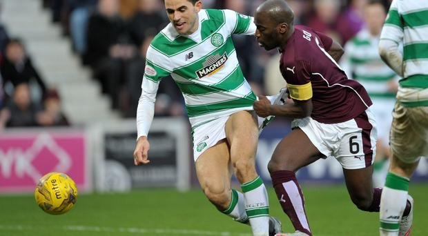 Race is on: Celtic's Tom Rogic and Morgaro Gomis of Hearts battle for the ball during the 2-2 draw at Tynecastle