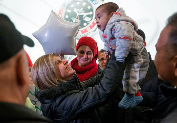 Tima Kurdi, left, who lives in the Vancouver area, lifts up her 5-month-old nephew Sherwan Kurdi after her brother Mohammad Kurdi and his family, who escaped conflict in Syria (Darryl Dyck/The Canadian Press via AP) MANDATORY CREDIT