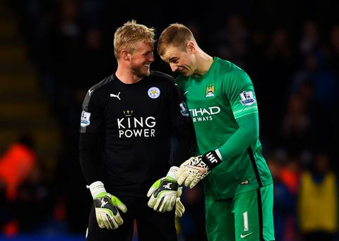 Glove story: Rival keepers Kasper Schmeichel (left) of Leicester City and Joe Hart of Manchester City share a joke after Premier League shock troops Leicester ended their amazing year level on points with league leaders Arsenal in an enthralling 0-0 draw at the King Power stadium last night