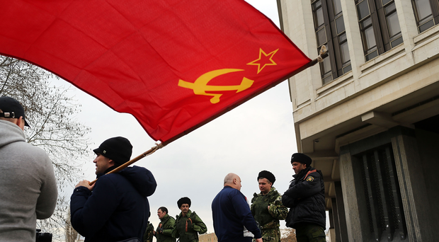 A man holds a Soviet era flag (Photo by Spencer Platt/Getty Images)