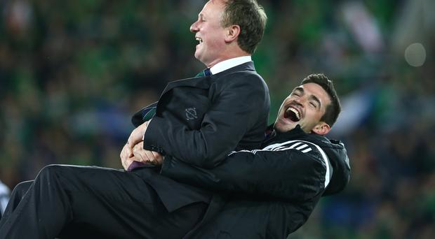 Kyle Lafferty lifts his Northern Ireland manager Michael O'Neill after the team qualified for Euro 2016