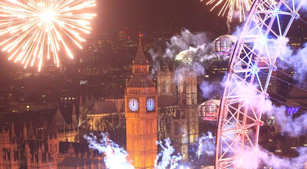 Fireworks light up the sky over the London Eye in central London during the New Year celebrations. PRESS ASSOCIATION Photo. Picture date: Friday January 1, 2016. Photo credit should read: Jonathan Brady/PA Wire