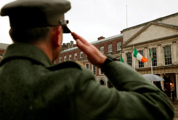 A member of the Irish defence forces salutes the National Flag which was flown from the GPO on O'Connell Street during the rebellion, as the first major event to mark the centenary of the 1916 Rising takes place at Dublin Castle in Ireland. PA