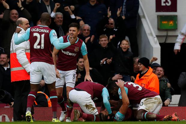 West Ham United's English striker Andy Carroll (2R) celebrates scoring his team's second goal with West Ham United's English midfielder Michail Antonio (R) during the English Premier League football match between West Ham United and Liverpool at The Boleyn Ground in Upton Park, East London on January 2, 2016. Getty Images