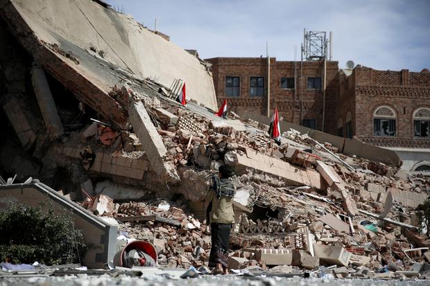 A man uses his mobile to take pictures of the rubble of the Chamber of Trade and Industry headquarters after it was hit by a Saudi-led air strike in Sanaa, Yemen, Tuesday, Jan. 5, 2016. (AP Photo/Hani Mohammed)