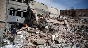 Employees walk on the rubble of the Chamber of Trade and Industry headquarters after it was hit by a Saudi-led airstrike in Sanaa, Yemen, Tuesday, Jan. 5, 2016. (AP Photo/Hani Mohammed)