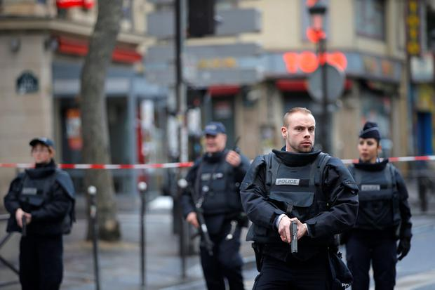 Police officers secure the perimeter near the scene of a fatal shooting which took place at a police station in Paris, Wednesday, Jan. 7, 2016. French officials say a man armed with a knife was shot to death by officers at a police station in northern Paris. Two officials say the man had wires extending from his clothing, and an explosives squad is on site. (AP Photo/Christophe Ena)