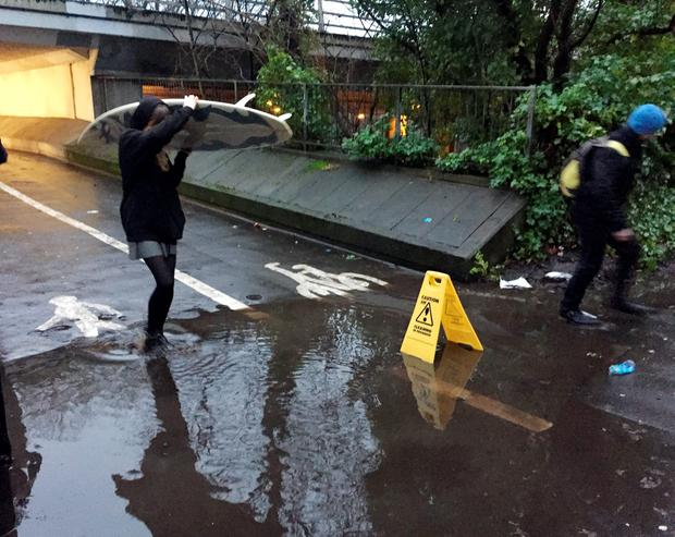 A person carrying a surfboard crosses the puddle outside Drummond Central in Newcastle upon Tyne, which became an internet sensation with tens of thousands of people watching it on Periscope. PA