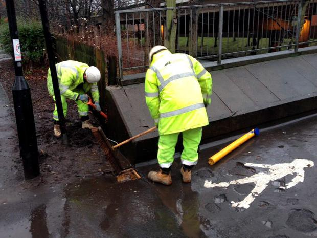 Handout photo issued by Newcastle City Council of workers clearing away a puddle outside Drummond Central in Newcastle upon Tyne. PA