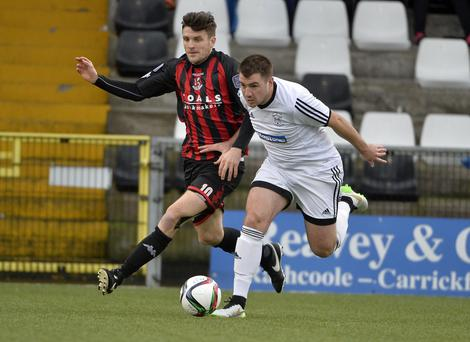 Crusaders' Diarmuid O'Carroll tussles with Rathfriland Rangers' Ross Black in their Tennent's fifth round clash at Seaview on Saturday