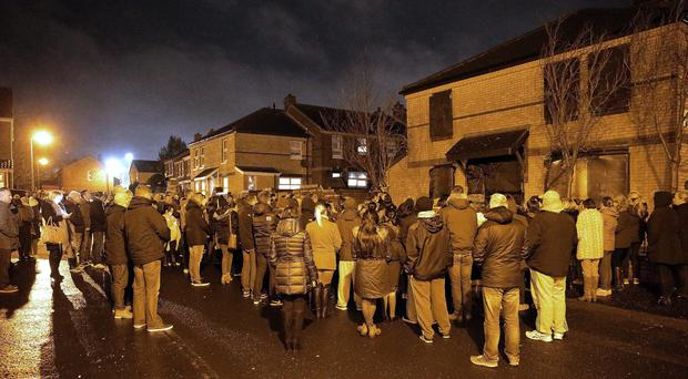 People gather for a vigil outside the home of 31-year-old Conor McKee who was shot at his Glenpark Street home in Belfast. Picture By: Pacemaker.