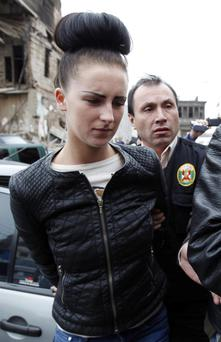 Michaella McCollum is escorted in handcuffs by police as she arrives to the Court in Callao, Peru