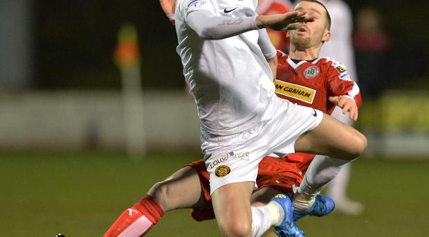 Thick of the action: Cliftonville's Martin Donnelly tackles Carrick Rangers ace Mark Surgenor at Solitude