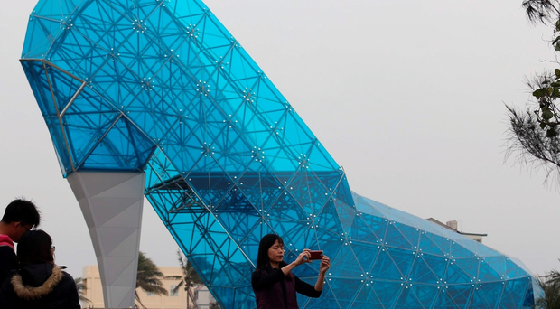 Tourists take pictures in front of a shoe-shaped church in southern Chiayi on January 11, 2016. The church, which measures 55 feet tall and 36 feet wide, took two months to build. Members of the public will be able to visit the exterior of the church before it is officially opened on February 8, 2018, before the lunar new year. AFP PHOTO / AFP / STRSTR/AFP/Getty Images