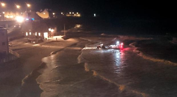Emergency workers during a rescue operation at Cullercoats, North Tyneside, last night, where a 15-year-old girl who was swept into the sea by a large wave.