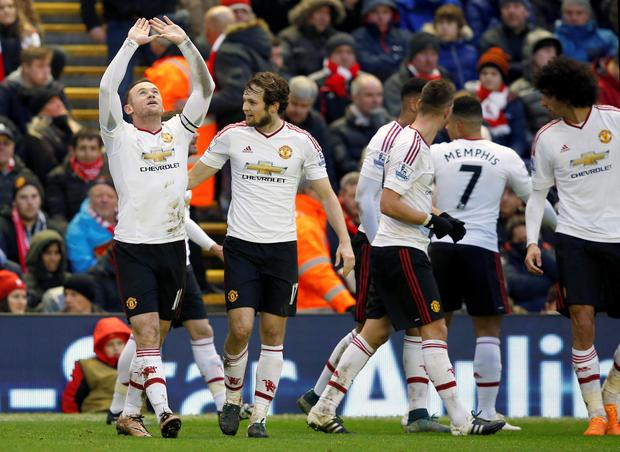 Manchester United's Wayne Rooney celebrates scoring his side's first goal with team mate Daley Blind during the Barclays Premier League match at Anfield, Liverpool.