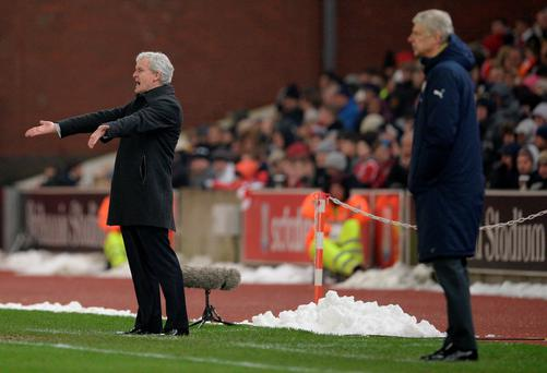 Arsenal's French manager Arsene Wenger (R) and Stoke City's Welsh manager Mark Hughes watch thier players during the English Premier League football match between Stoke City and Arsenal at the Britannia Stadium in Stoke-on-Trent, central England on January 17, 2016.