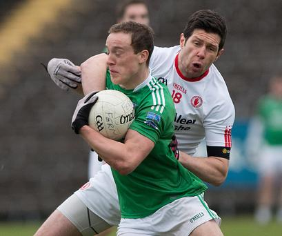 Gripping affair: Fermanagh's Che Cullen is tackled by Sean Cavanagh