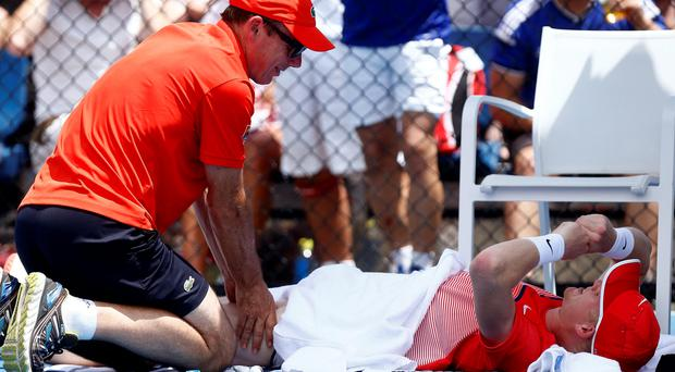 Down and out: British ace Kyle Edmund is treated for cramp during his five-set loss to Damir Dzumhur in the first round of the Australian Open