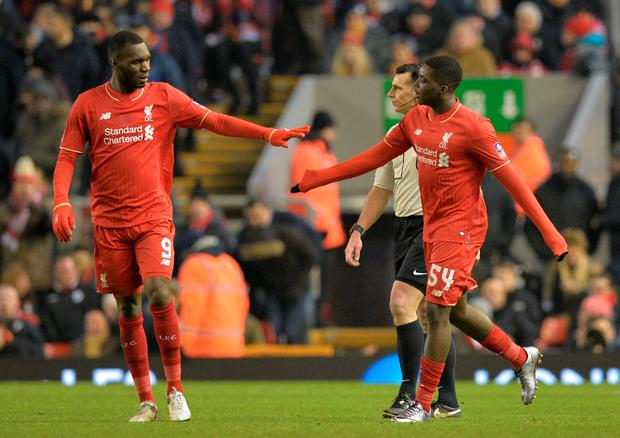 Liverpool's English midfielder Oluwaseyi Ojo (R) is congratulated by Liverpool's Zaire-born Belgian striker Christian Benteke (L) after he scores their second goal during the English FA Cup third round replay football match between Liverpool and Exeter City at Anfield in Liverpool, north west England on January 20, 2016. AFP/Getty Images