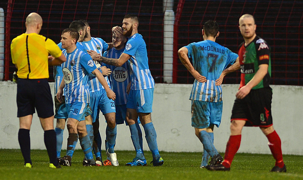 Pointing the way: Martin Murray is mobbed by his Warrenpoint team-mates after hitting a double against Glentoran