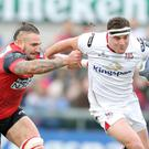 Holding on: Ulster's Rob Herring is tackled by Oyonnax's Pierrick Gunther while Craig Gilroy goes over for a try