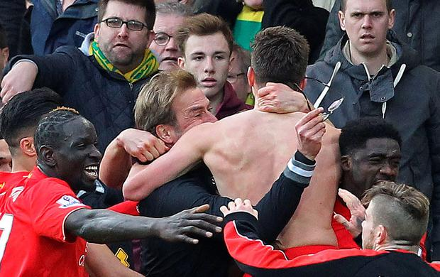 With his shirt off, Liverpool's English midfielder Adam Lallana celebrates scoring their late winning goal with Liverpool's German manager Jurgen Klopp (C) holding his glasses during the English Premier League football match between Norwich City and Liverpool at Carrow Road in Norwich, eastern England, on January 23, 2016. Liverpool won the game 5-4. AFP/Getty Images