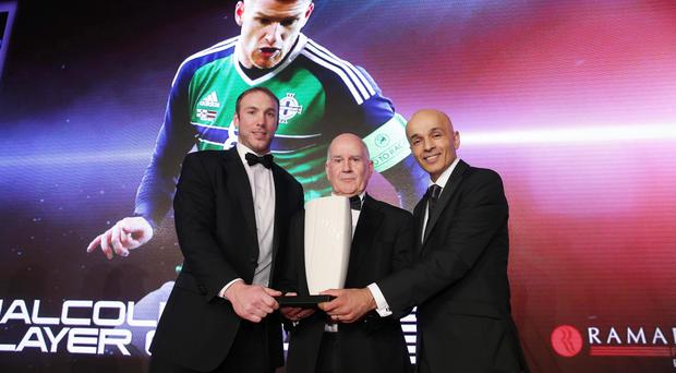 Malcolm Brodie Player of the Year: Steven Davis (collected by father David) .Rugby Legend Stephen Ferris and Rajesh Rana, Director of category sponsor Ramada Plaza presents David Davis with Stephen's trophy. Picture by Kelvin Boyes/ Press Eye