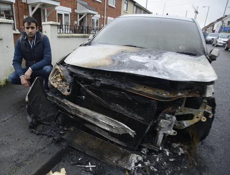 Daniel Cirpaci looks at the damage cause to his car after it was set alight in the Ebor Street area of Belfast on Tuesday Morning, The Fire service attended the scene. Pic Colm Lenaghan/Pacemaker