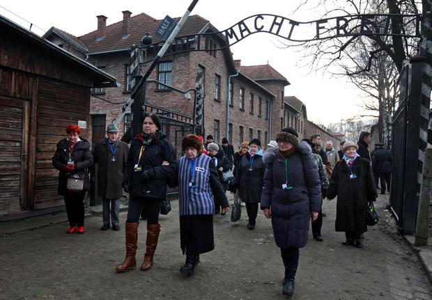 Holocaust survivors walks with others through the main gate of the former Auschwitz Nazi death camp in Oswiecim, Poland, Wednesday, Jan. 27, 2016, the 71st anniversary of the death camp's liberation by the Soviet Red Army in 1945. (AP Photo/Czarek Sokolowski)