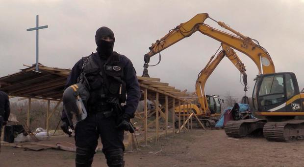In this frame grab from APTN taken on Monday Feb. 1, 2016, a policeman stands guard as a mechanical digger destroys a makeshift church at a migrant camp in Calais, France. (AP Photo/APTN)