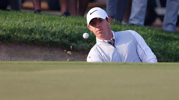 Eyes on prize: Rory McIlroy plays his third shot in the first round of the Dubai Desert Rory finds Classic at Emirates Golf Club