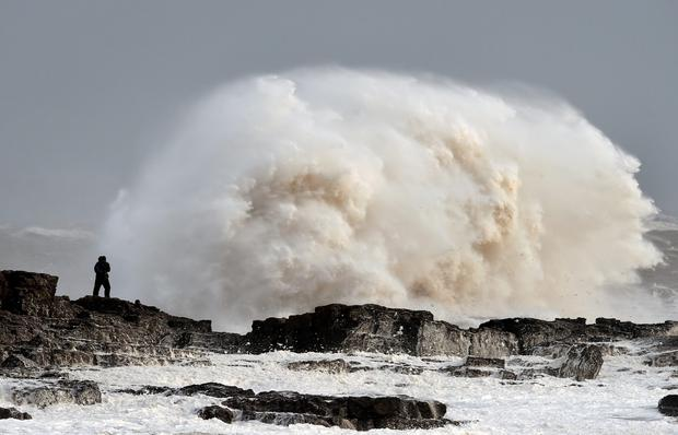 Waves crash over rocks at Porthcawl in Wales as winds of nearly 100mph battered Britain after Storm Imogen slammed into the south coast bringing fierce gusts and torrential downpours. PA