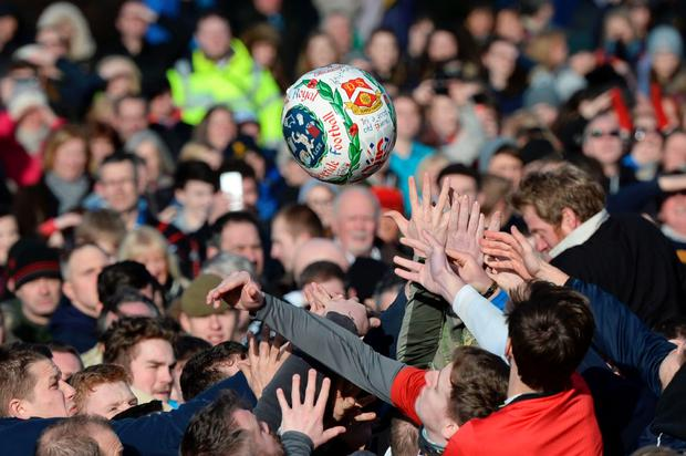 Competitors reach for the ball after it is 'turned up' to start the annual Royal Shrovetide Football Match in Ashbourne, northern England, on February 9, 2016 between the two opposing team's, the Up'ards and the Down'ards. AFP/Getty Images