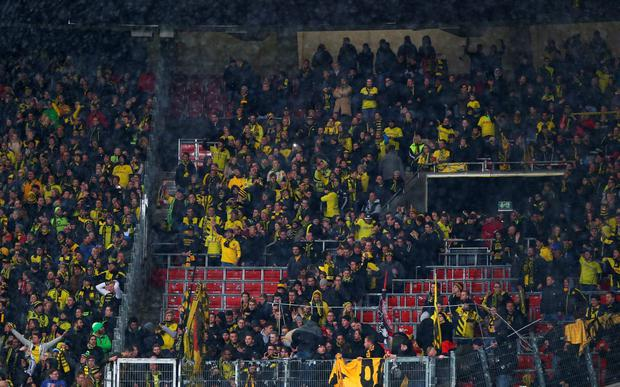 Borussia Dortmund fans return to their seats after a protest about ticket prices during the DFB Cup Quarter Final match between VfB Stuttgart and Borussia Dortmund at Mercedes-Benz Arena on February 9, 2016 in Stuttgart, Germany. (Photo by Alex Grimm/Bongarts/Getty Images)