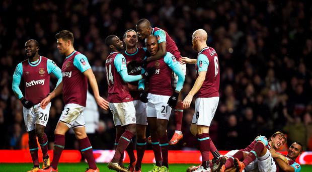 Nick of time: Angelo Ogbonna is mobbed after powering home a last-gasp header to send West Ham through at Liverpool's expense