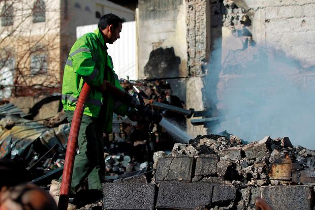 A Yemeni firefighter extinguishes smoke rising from buildings destroyed in an air-strike by the Saudi-led coalition on February 10, 2016 in the capital Sanaa. / AFP / MOHAMMED HUWAISMOHAMMED HUWAIS/AFP/Getty Images