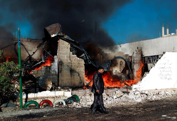 A Yemenis man walks past flames rising from the ruins of buildings destroyed in an air-strike by the Saudi-led coalition on February 10, 2016 in the capital Sanaa. / AFP / MOHAMMED HUWAISMOHAMMED HUWAIS/AFP/Getty Images