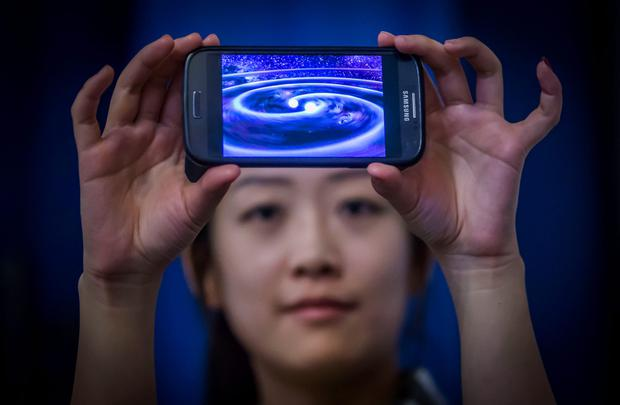 Student Muzi Li at the Institute of Gravitational Research at Glasgow University holding a phone that shows a computer simulation of gravity waves - ripples in spacetime - which have been detected by scientists a century after Albert Einstein predicted their existence. PA