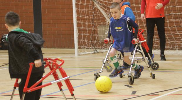 GAME ON: Oliver Dickey playing Frame Football and (left) some of the other players and their trainers at the Loughshore Recreation Centre. Pic: Colm O'Reilly/Sunday Life.