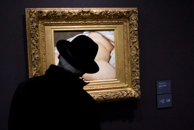 A visitor looks at Gustave Courbet's 1866